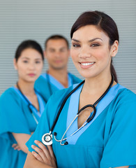 Attractive female doctor with his colleagues in the background
