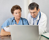 Doctor and Nurse Reviewing on Laptop Computer in Office poster