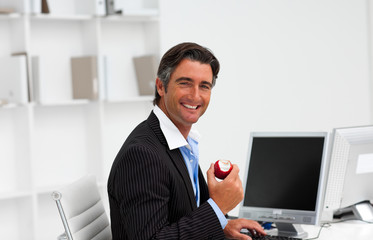 Businessman eating a fruit at work