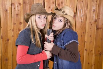 girls blowing on shotgun barrel