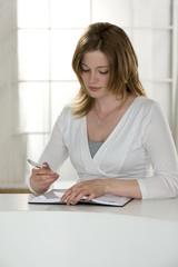 Frau schreibt in einen Terminkalender