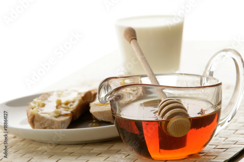 Pot of honey, glass of milk and bread