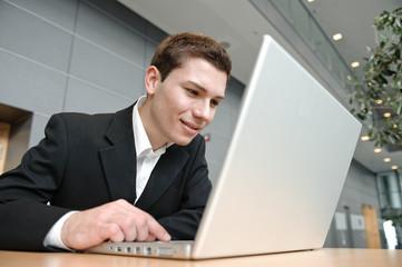 erfolgreicher geschäftsmann surft mit laptop in büro