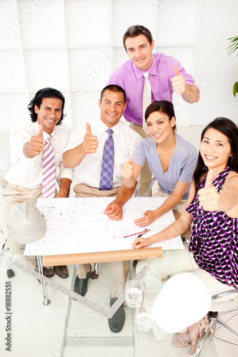 A group of architects with thumbs up in a meeting