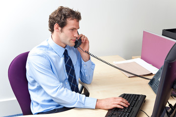 Customer support worker in an office on the telephone