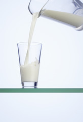 Pouring milk into a glass using a carafe