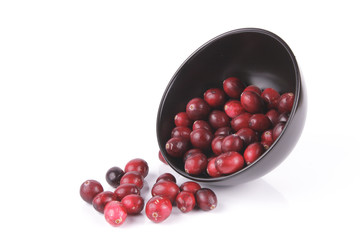 Cranberries spilling out of a Black Bowl