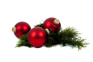 Red Christmas ornaments/baubles with pine branch on white