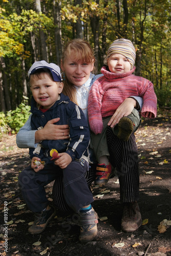 Happy family of mother and two sons in autumn forest