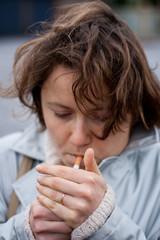 Femme qui allume une cigarette