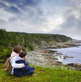 Children sitting at Atlantic coast in Newfoundland poster