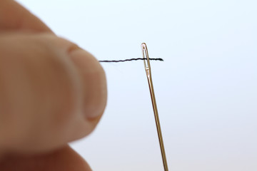 Close up of a thread being threaded through a needle hole.