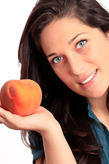 Beautiful young girl holding a peach.