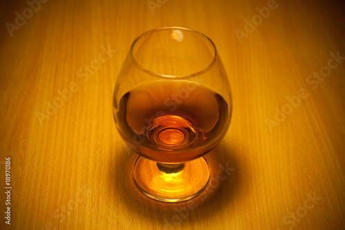 glass of cognac close-up on wooden background