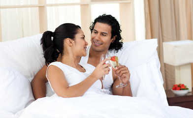 Lovers toasting with Champagne in the bedroom