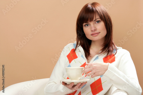 Young woman sitting in armchair with cup of tea