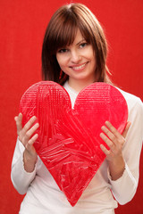 Happy woman holding big red heart on red background