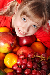 Child girl in group of fruit.