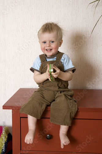 blond smiling boy sitting on bureau
