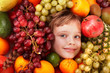 Child girl in group of fruit. Isolated.