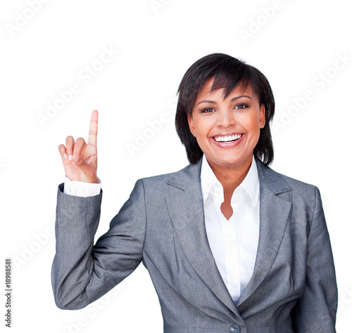 Businesswoman pointing upwards smiling at the camera