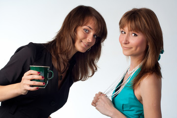 Two girls holds a cup of tea