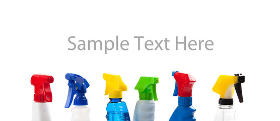 a row of assorted cleaning trigger bottles with copy space
