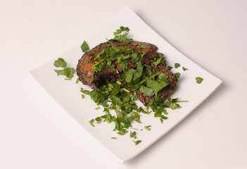 Roast chicken with fresh herbs on a white plate