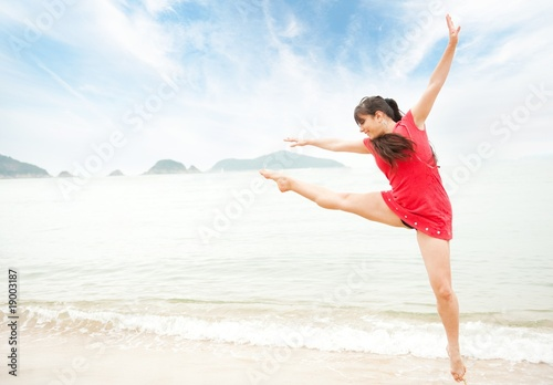Beautiful young woman jumping in the sea .
