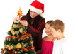Mother and children decorating Christmas tree, studio shot