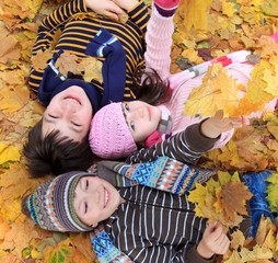 Children lying in fall leaves