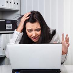 Eine junge Frau verzweifelt an einem Computerprob