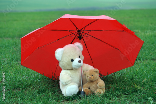 Two teddy bears under red umbrella