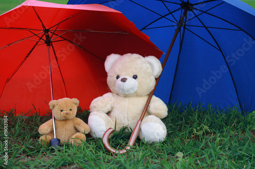 Two teddy bears under red and blue umbrella