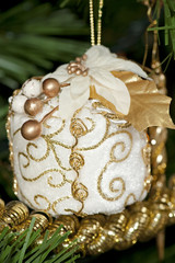 Close-up of a decorative golden bauble on the Christmas tree