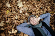 Young handsome man lying on autumn background