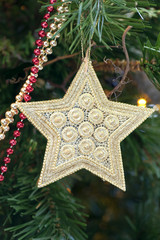 Golden decorative star hanging on the Christmas tree