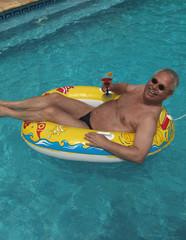 älterer Mann im Urlaub, Swimmingpool, Schlauchboot