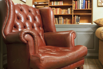 Old style armchair in front of bookshelves