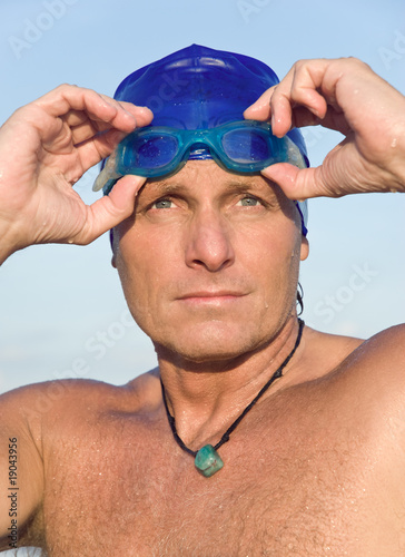 pensive looking male swimmer on beach