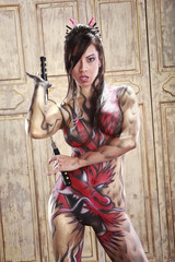 Asian girl in bodypainting with nunchuks