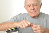 Elderly man cleans his fingernail with screwdriver poster