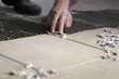 Close up of hand of worker putting tiles on the floor.