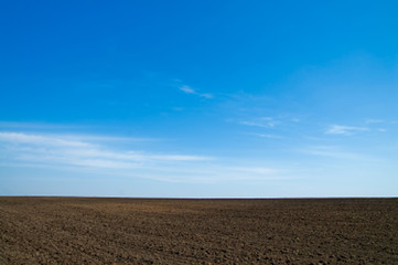 black field after harvesting under blue sky