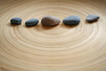 Steine in Linie auf Holz