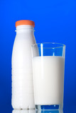 Milk in glass and bottle isolated on blue