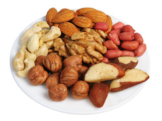 Set of nuts on a white plate, isolated