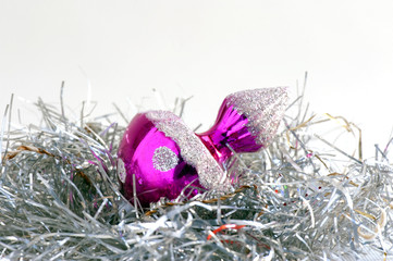 Close-up of a shiny pink Christmas bauble on a silver tinsel