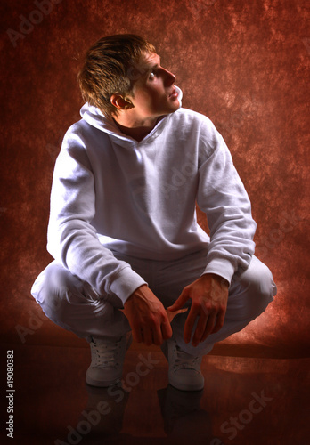 smiley guy sitting on the floor against dark background..