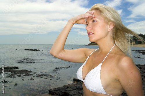 Sexy blonde model relaxes by the beach